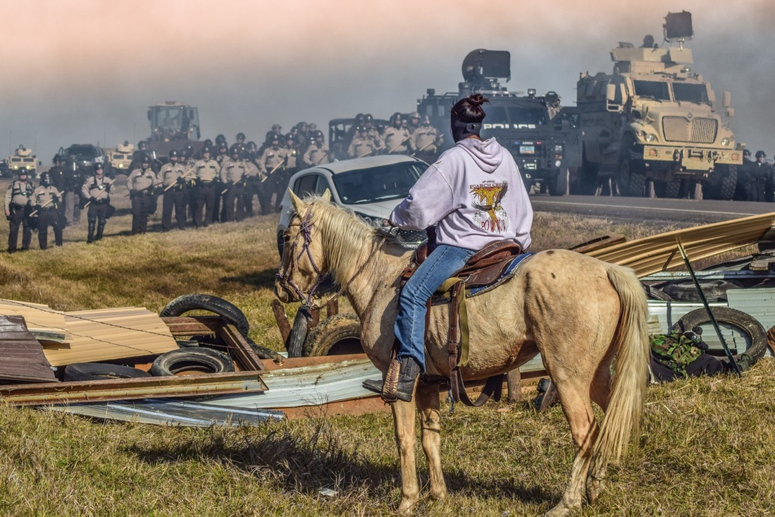 Ryan Vizzions, Defend the Sacred (An indigenous water protector on horseback sits face-to-face with a brigade of police officers), October 27, 2016 (© Ryan Vizzions)